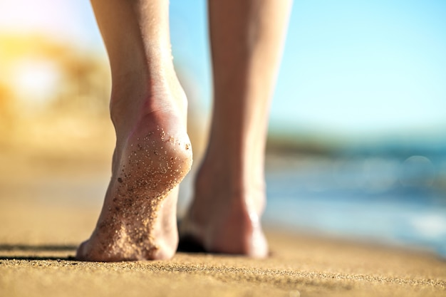 Pies de mujer caminando descalzo sobre la arena dejando huellas