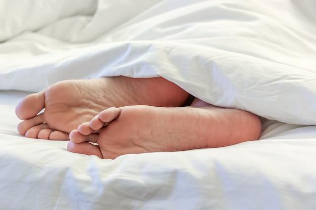 Pies de mujer dormida en la cama
