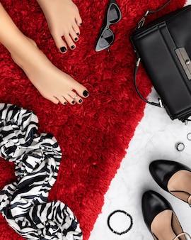 Pies de mujer hermosa arreglada con diseño de uñas negras en colcha peluda roja. manicura, concepto de salón de belleza de pedicura.