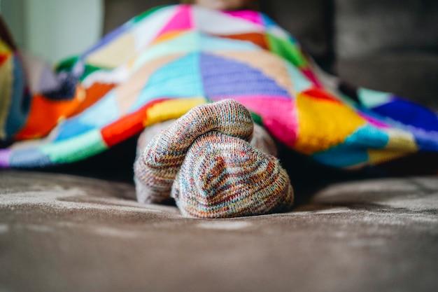 Pies de una mujer con medias en un sofá marrón cubierto con una manta de retazos