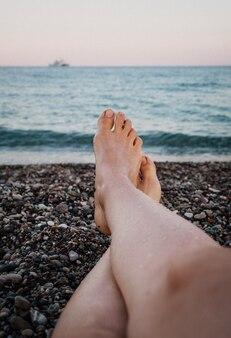 Pies de la mujer del primer en una playa de piedra del guijarro contra el mar en un día de verano. mujer joven tiene descanso.