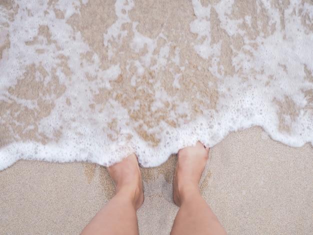 Pies de la mujer de selfie en fondo de la playa del verano.