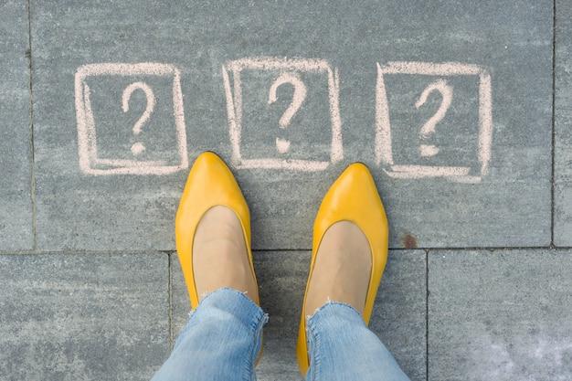 Pies de mujer con signos de interrogación delante de sus piernas