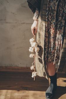 Pies de las mujeres en ropa de lino y zapatos al lado de una flor sobre un fondo blanco