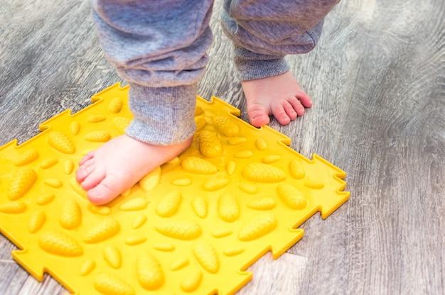 Los pies del niño en el primer plano de la estera ortopédica.