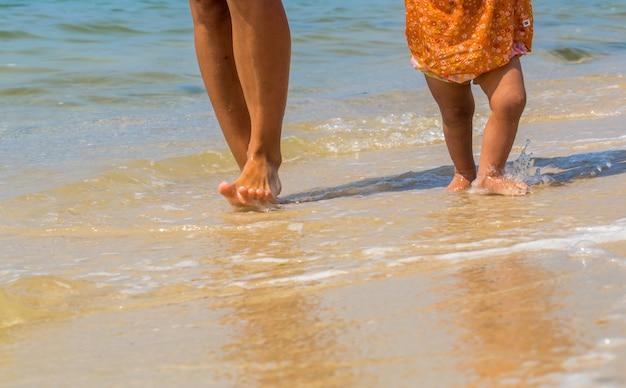 Pies de niños y adultos en la playa, una madre con un hijo, familia