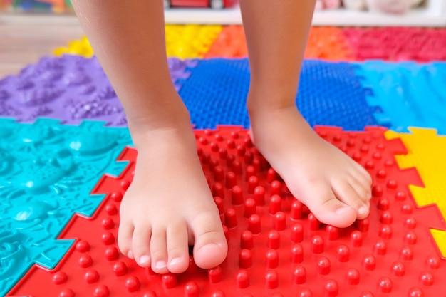 Pies de niños sobre colchonetas ortopédicas, prevención de pies planos.