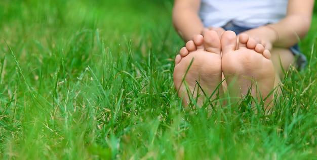 Pies de los niños sobre la verde hierba en el parque.