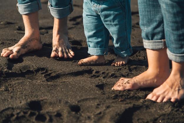 Pies de los padres y el bebé de pie en la playa de arena