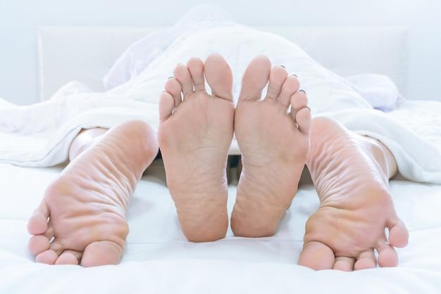Los pies de parejas que sobresalen de debajo de duvet o blanket hacen el amor en casa en el dormitorio