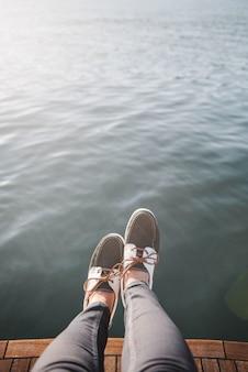 Pies de la persona en el barco navegando por el mar durante el día