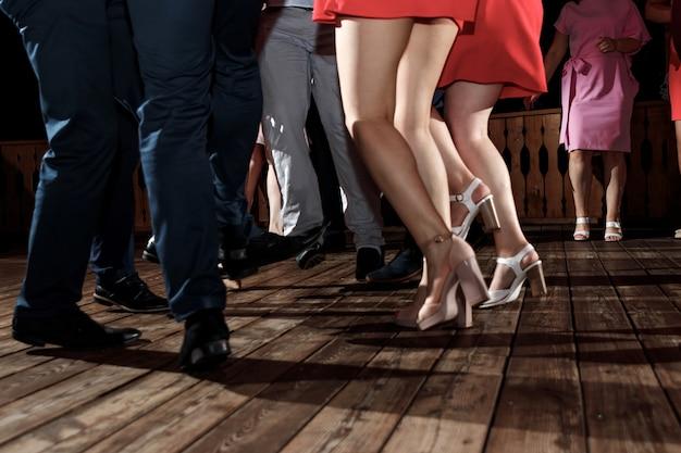 Pies de personas bailando en una fiesta del club. irreconocible