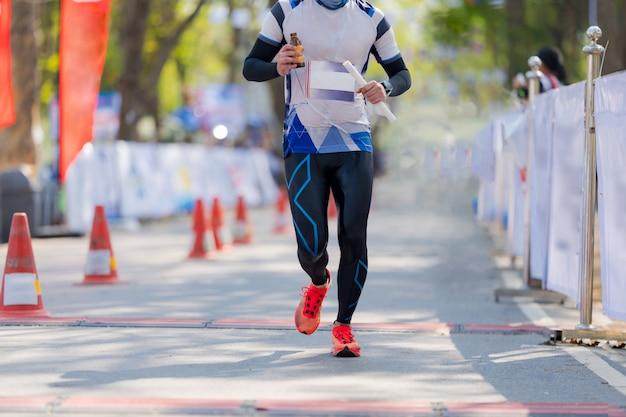Pies de personas, maratón corriendo en las calles del parque
