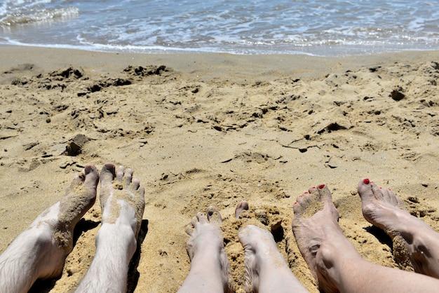 Pies de personas tumbadas en la arena