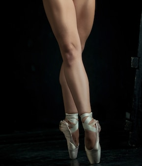 Los pies de primer plano de la joven bailarina en zapatillas de punta contra el fondo negro