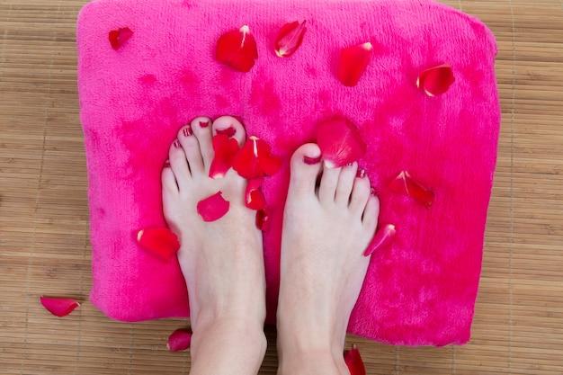 Pies sobre almohada con pétalos de rosa