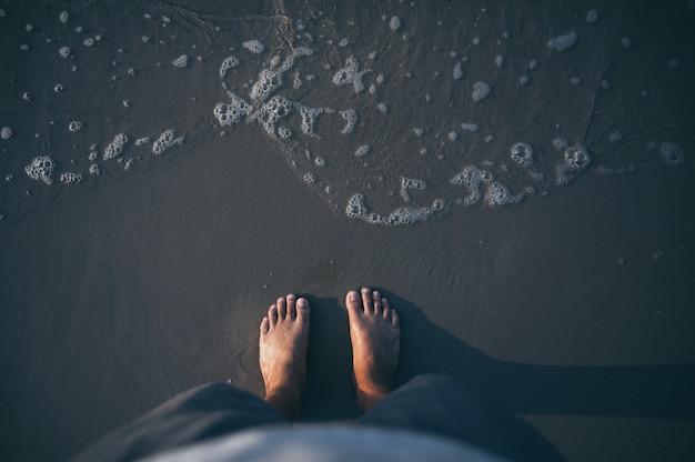 Pies sobre arena de mar y olas