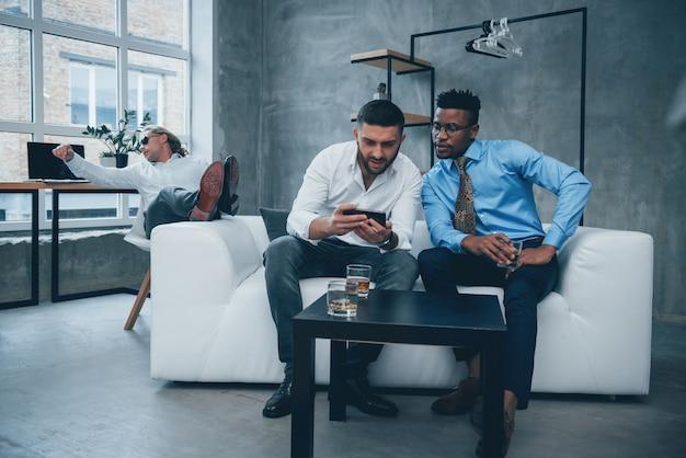 Pies en el sofá. tiempo de relajación. grupo de trabajadores de oficina multirraciales en ropa formal hablando sobre tareas y planes