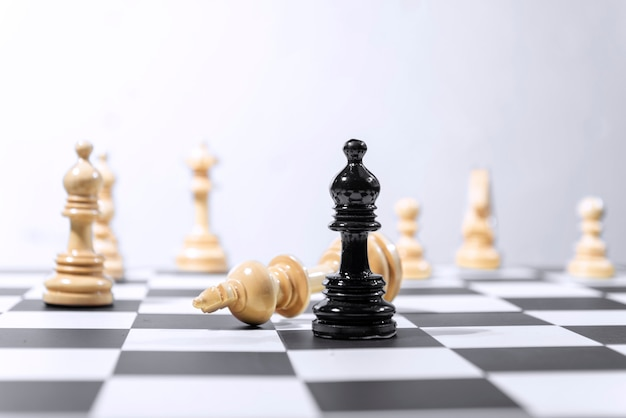 Pieza de ajedrez rey de madera derrotada por pieza de ajedrez obispo negro