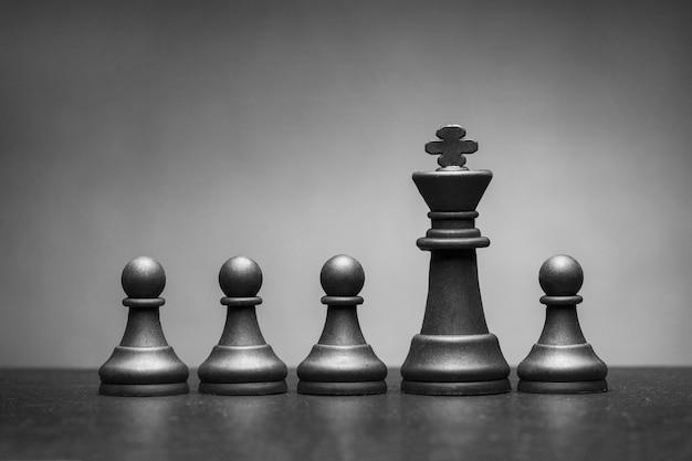 Pieza de ajedrez rey negro con cuatro peones