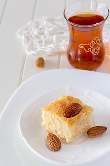Pieza basbousa torta de sémola árabe tradicional con nueces flor de azahar agua espacio de copia vertical fondo blanco