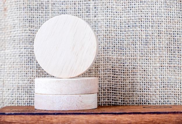 Pieza en blanco de madera redonda en mesa de madera y pared de tela de saco