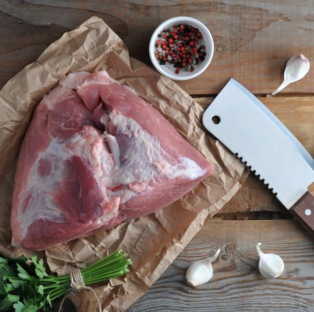 Pieza cruda de jamón grande de cerdo y un gran cuchillo para picar