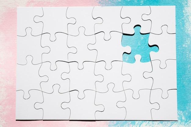 Pieza faltante del rompecabezas blanco sobre superficie de color dual.