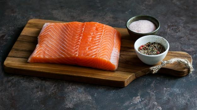 Pieza fresca cruda de salmón en la tabla de cortar