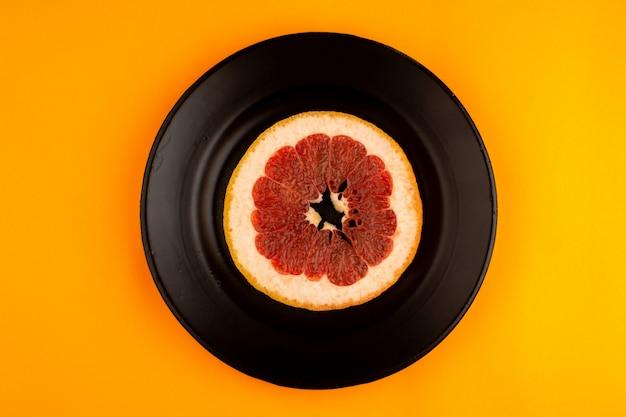 Pieza de pomelo redondo fresco jugoso suave dentro de un plato negro sobre la naranja