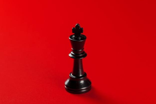 Pieza del rey ajedrez negro sobre fondo rojo.