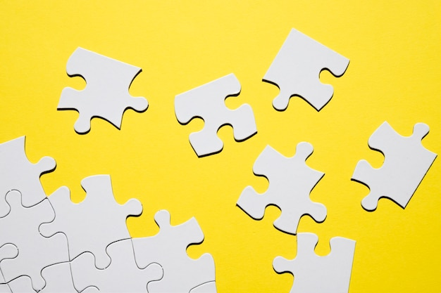 Pieza del rompecabezas blanco separado sobre fondo amarillo