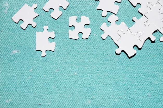 Pieza del rompecabezas blanco sobre superficie texturizada azul