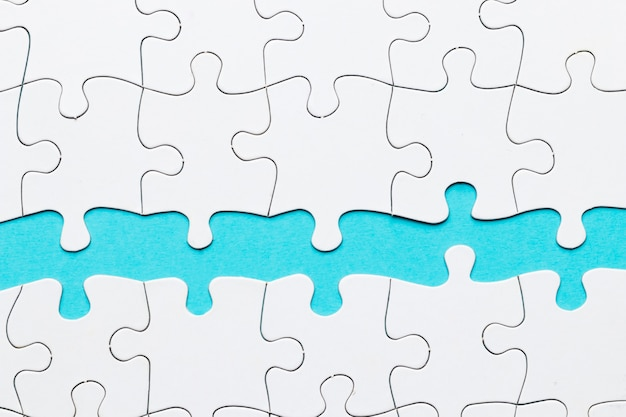 Pieza del rompecabezas contra sobre fondo azul