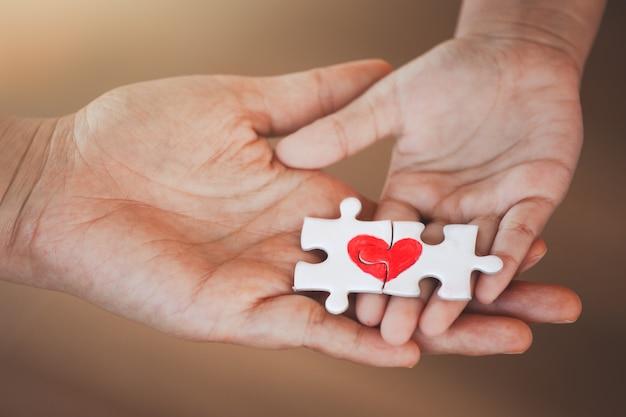 Pieza del rompecabezas de la pareja con el corazón rojo dibujado puesto en la mano del padre y del niño