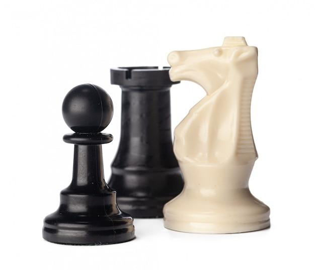 Piezas de ajedrez en blanco y negro sobre fondo blanco.