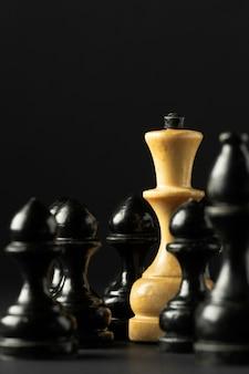 Piezas de ajedrez en blanco y negro sobre fondo negro