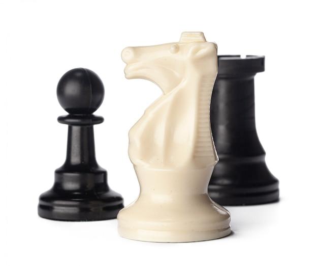 Piezas de ajedrez en blanco y negro sobre superficie blanca