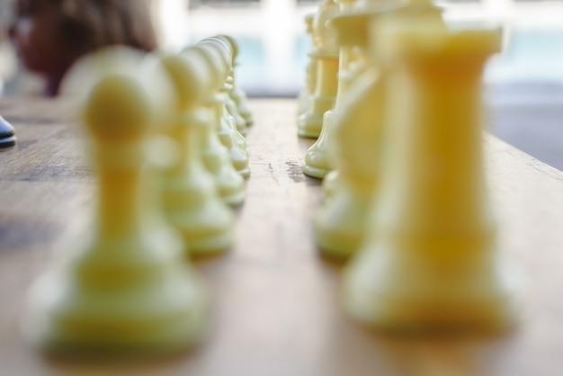 Piezas de ajedrez defocused blancas y tablero de madera.