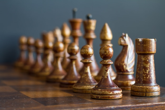 Piezas de ajedrez de madera vintage en un viejo tablero de ajedrez.