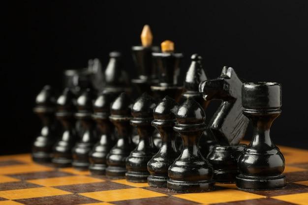 Piezas de ajedrez negras sobre tablero de ajedrez.
