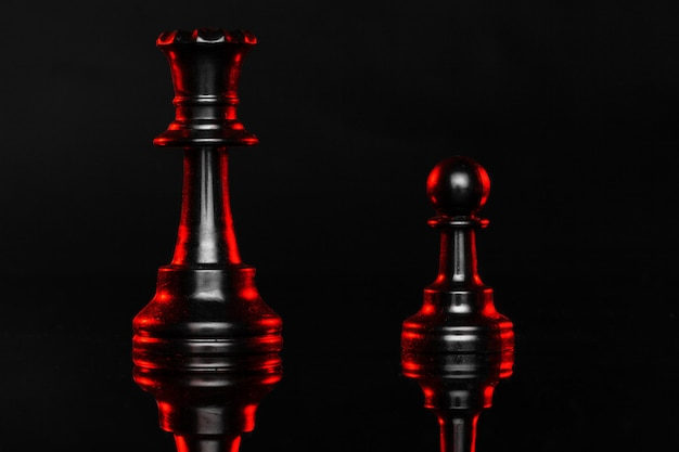 Piezas de ajedrez en la oscuridad con luz de fondo roja de cerca
