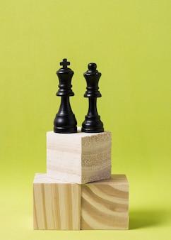 Piezas de ajedrez rey y reina en cubos de madera a la misma altura