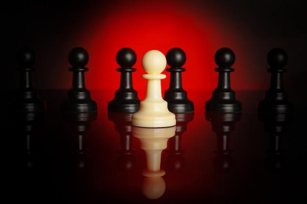 Piezas de ajedrez sobre fondo oscuro con luz de fondo roja de cerca