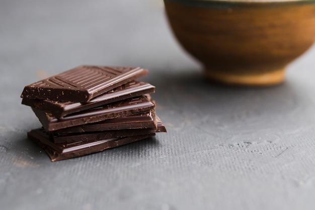 Piezas apiladas de barra de chocolate roto en la mesa gris