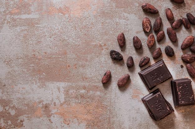 Piezas de chocolate con granos de cacao en bruto en el fondo rústico