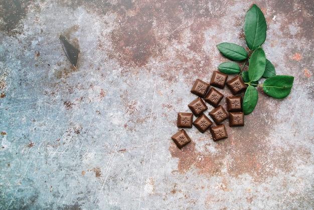 Piezas de chocolate con hojas sobre fondo rústico grunge