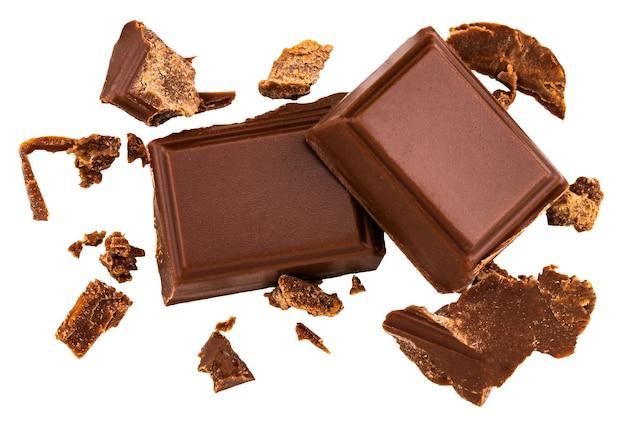 Piezas de chocolate con leche aisladas sobre fondo blanco desde la vista superior.
