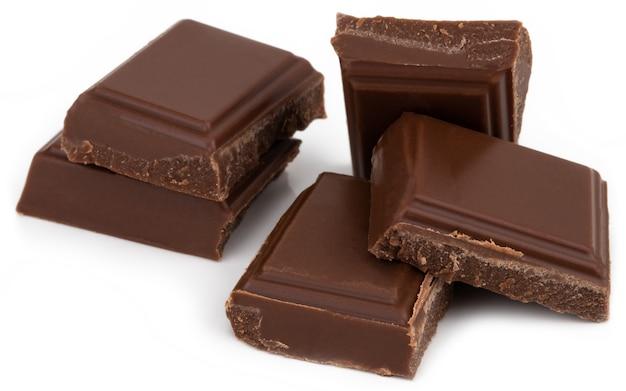 Piezas de chocolate con leche aisladas sobre fondo blanco.