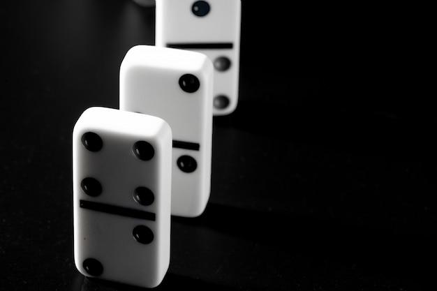 Piezas de dominó colocadas en una fila sobre fondo negro